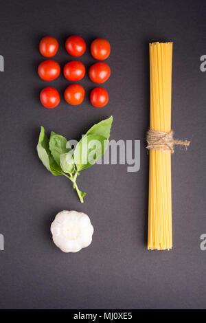 Kulinarische Rezept Konzept. Spaghetti gebunden mit einem Seil mit Cherry Tomaten, Knoblauch und Basilikum auf schwarzem Hintergrund. Flach - Stockfoto
