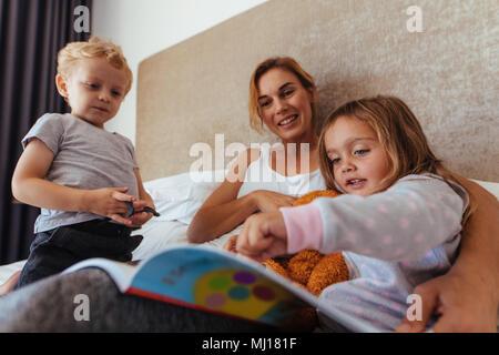 Junge Mutter mit ihren Kindern im Bett und liest ein Buch. Süße kleine Mädchen zeigen auf Storybook beim Sitzen mit ihrer Mutter und ihrem Bruder auf dem Bett. - Stockfoto