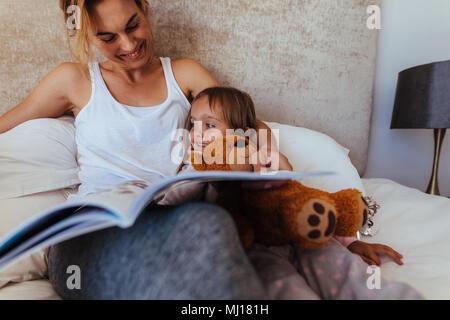 Happy Family lesen Gute-Nacht-Geschichte im Bett. Frau auf der Suche nach ihrer Tochter und Lächeln beim Lesen eines Buches im Schlafzimmer. - Stockfoto