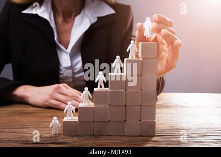 Der Unternehmer Hand menschlichen Figuren auf der Treppe Aus Holzklötzen - Stockfoto