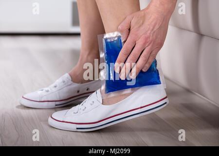 Nahaufnahme der Frau Hand Cool Gel Pack auf Ihrem Knöchel - Stockfoto