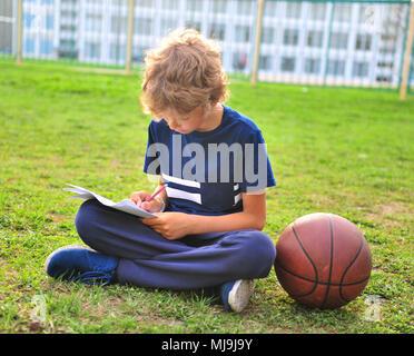 Junge mit Papier und Basketball auf dem Gras - Stockfoto