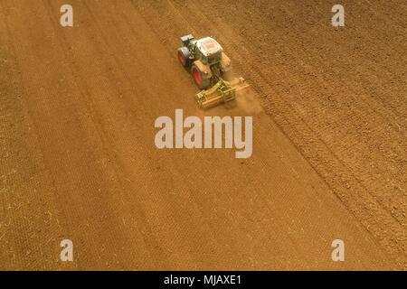 Luftaufnahme der Landwirt mit einem Traktor auf den landwirtschaftlichen Bereich Aussaat. Traktoren Arbeiten im landwirtschaftlichen Bereich im Frühjahr. Baumwollsamen - Stockfoto