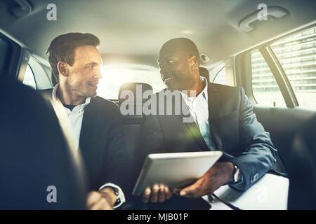 Zwei lächelnde diverse Geschäftsleute auf dem Rücksitz eines Autos sitzt mit einem Tablet, während durch die Stadt fahren - Stockfoto