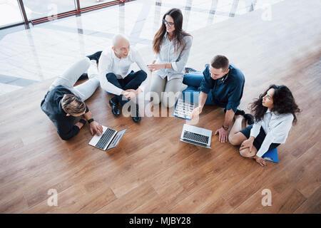 Junge kreative Menschen in modernen Büro. Die Gruppe junger Geschäftsleute gemeinsam mit Laptop. Freiberufler sitzen auf dem Boden. Zusammenarbeit - Stockfoto