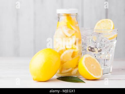 Glas Flasche Zitrone noch Obst Wasser, Limonade und Glas mit Eiswürfel und raw Orangen auf weißem Holz- Hintergrund - Stockfoto