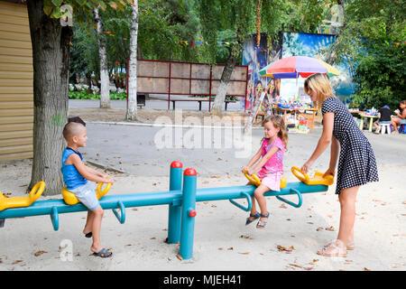 Krasnodar, Russland - 28. August 2017: Eine junge Mutter spielt mit den Kindern auf dem Spielplatz. - Stockfoto