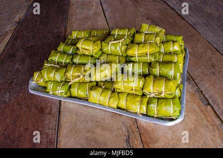 Bananen mit klebrigen Reis mit Blatt auf braunem Holz- Hintergrund gewickelt. Khao Tom Mat. - Stockfoto