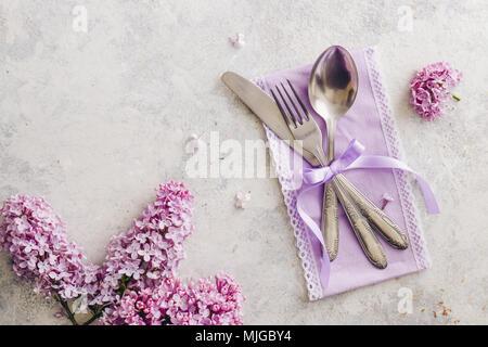 Frühling Tischdekoration mit lila Blüten. Elegante Tischdekoration mit lila Blüten, violett serviette und vintage Besteck auf rustikalen Hintergrund. - Stockfoto