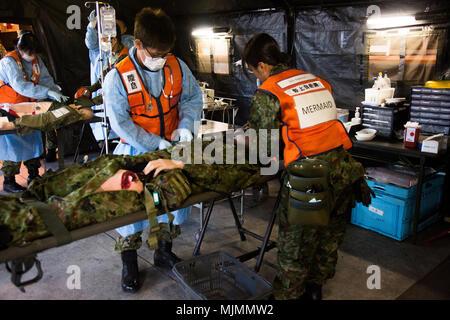 Japan Ground Self Defense Force Soldaten mit der medizinischen Abteilung, Boden Personal Office, Westliche Armee, medizinische Fähigkeiten zu US-Mitglieder demonstrieren, während einer Messe- und Unfallversicherung Szenario Dez. 12, 2017, am Lager Naha, Okinawa, Japan. Medizinisches Personal ab 3. Medizinischen Bataillon, 3. Marine Logistics Group; U.S. Naval Hospital Okinawa; und 18 medizinische Gruppe, 18 Wing Support Squadron lagerten Naha während der japanischen und US-amerikanischen medizinischen Sachverständigen Exchange Event training Mehr über Medizinische jedes Service Training, Taktik und Verfahren zu erlernen, eingeladen. (U.S. Marine Corps Foto von Lance Cpl. Ich - Stockfoto