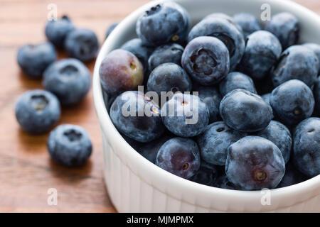 Kleine weiße Schüssel gefüllt mit frischen Blaubeeren, sechs Blaubeeren auf der linken Seite, Holzplatte Hintergrund, gesunde Ernährung Konzept - Stockfoto