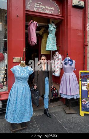 Eine junge Frau verlassen von Armstrong Vintage Clothing Store in den Grassmarket, Edinburgh, Schottland, Großbritannien. - Stockfoto