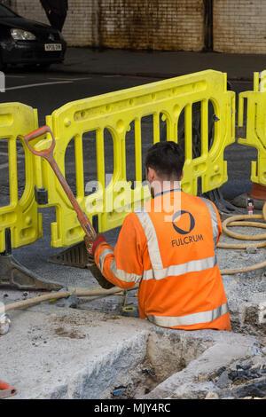 Ein Mann mit hoher Sichtbarkeit orange Kleidung arbeiten graben ein Loch in der Straße bis zu hos Taille in verwöhnen mit einer Schaufel hinter Gelb Barrieren. - Stockfoto