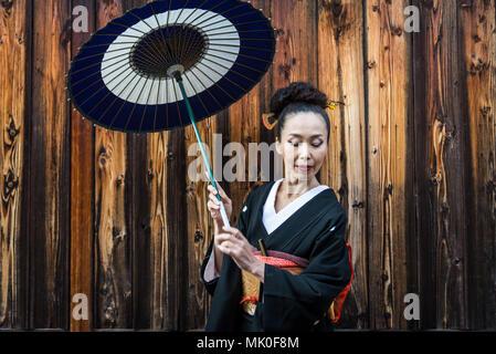 Japanische Frau, die traditionelle Kleidung und Walking im Freien - Stockfoto