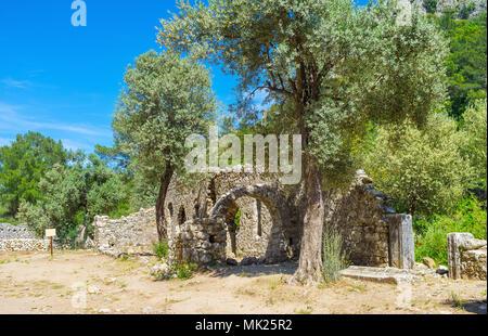 Die steinerne Ruinen in archäologische Stätte des antiken lykischen Stadt Olympos, in River Valley am Berg gelegen, in der Nähe der Küste, Türkei. - Stockfoto