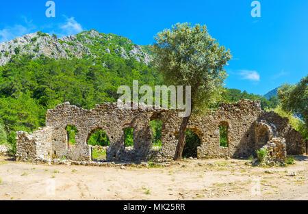 Die landschaftlich schöne steinerne Ruinen in den üppigen Vegetation im Tal umgeben von den Rocky Mountains, Türkei. - Stockfoto