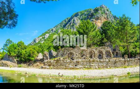 Die Ruinen des antiken Badehaus am Ufer der Stream mit üppigen Nadelwald und Rocky Mountain auf den Hintergrund, Olympos, Türkei. - Stockfoto