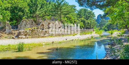 Auf schattigen Bank von Olympos Stream mit Blick auf die antiken Ruinen der Thermen in archäologische Stätte Olympos, Türkei entspannen. - Stockfoto