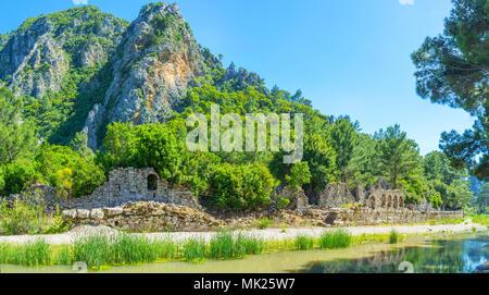 Das malerische Tal des Flusses mit Blick auf den Bach, alte Ruinen, grünen Wald und steile Felsen auf dem Hintergrund, Olympos, Türkei. - Stockfoto