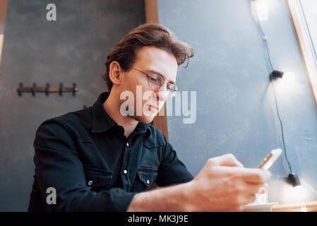 Portrait gut aussehender bärtiger Mann Kopfhörer video Mobiltelefon moderne Loft Studio. Mann in vintage Stuhl, Smartphone und entspannend. Horizontale, Film, Bokeh - Stockfoto