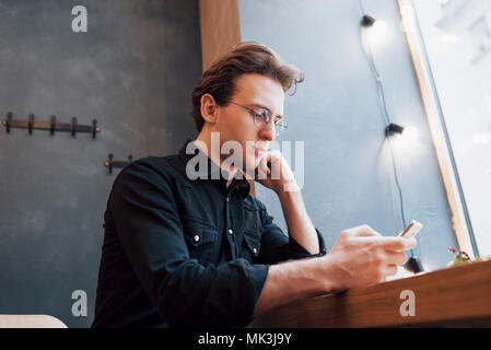Soft Focus. Mann hält und mit Phone verkaufen. beim Sitzen und auf dem Sofa im modernen Haus entspannen. Konzept für junge Menschen, die mobiles Gerät