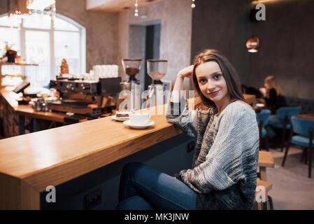 Attraktive junge Frau sitzt innen in städtischen Cafe. Cafe Stadt Lebensstil. Casual Portrait von jugendlichen Mädchen. Getönt. - Stockfoto
