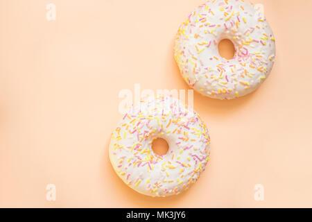 Donut mit weißer Zuckerglasur farbige Topping, auf gelben Hintergrund isoliert. Lecker Klassiker zwei verglaste Donuts isoliert. Leckere bunte Donuts - Stockfoto