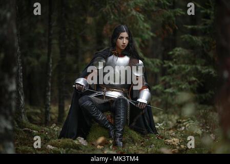 Einen schönen Krieger Mädchen mit einem Schwert tragen Kettenhemden und Rüstung in einen mysteriösen Wald