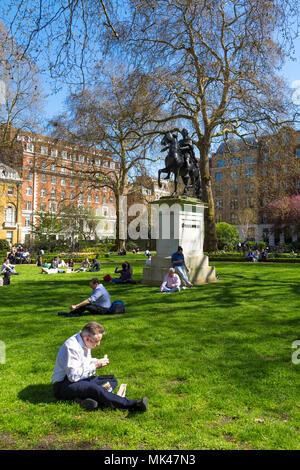 Leute sitzen auf das Gras und das Mittagessen in einem kleinen Stadtpark, St James's Square Garden, London, UK - Stockfoto