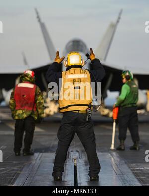 171113-N-JH 929-115 WESTERN PACIFIC (Nov. 13, 2017) Segler Durchführung Flugbetrieb auf dem Flugdeck an Bord der Flugzeugträger USS Nimitz (CVN 68). Der Nimitz Carrier Strike Group ist in regelmäßigen Bereitstellung in den USA 7 Flotte Bereich für Maßnahmen zur Erhöhung der Sicherheit des Seeverkehrs und Theater Sicherheit Bemühungen um Zusammenarbeit. Der US-Pazifikflotte hat den Indopazifischen routinemäßig für mehr als 70 Jahre patrouillierten die regionale Sicherheit, Stabilität und Wohlstand. (U.S. Marine Foto von Mass Communication Specialist 3. Klasse Cole Schroeder/Freigegeben) - Stockfoto