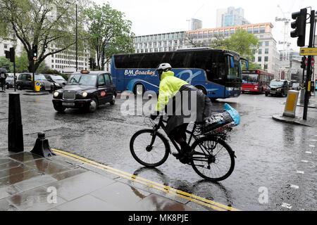 Eine männliche Radfahrer tragen Regenmantel und Sturzhelm Zyklen über die Kreuzung Ampel im Regen auf einer belebten Straße in der City von London UK KATHY DEWITT - Stockfoto