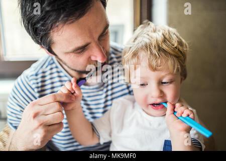 Vater seine Zähne putzen mit einem Kleinkind Junge zu Hause. - Stockfoto