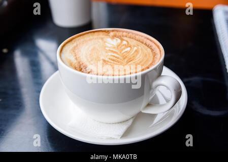 Cappuccino in einem weißen Schale am Tisch im Restaurant - Stockfoto