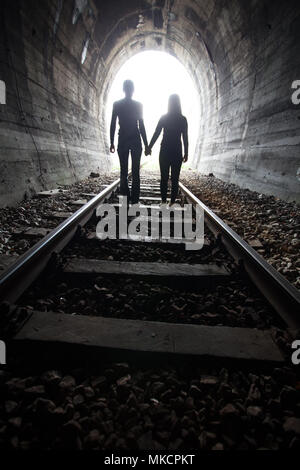 Paar Hand in Hand entlang der Strecke durch eine Eisenbahn Tunnel Richtung helles Licht am anderen Ende, erscheinen sie als Silhouetten gegen die - Stockfoto