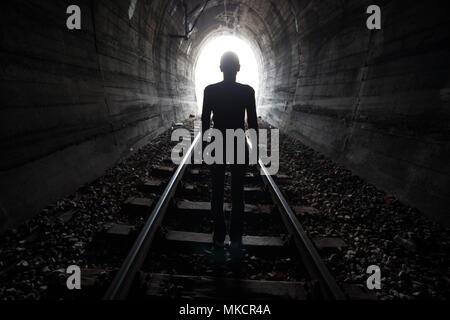 Mann Silhouette, die in einem Tunnel in der Mitte der Gleise mit Blick auf das Licht am Ende des Tunnels in einem konzeptionellen Bild - Stockfoto