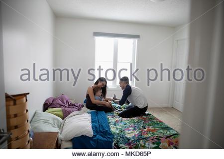 Junge Familie entspannen auf Bett - Stockfoto