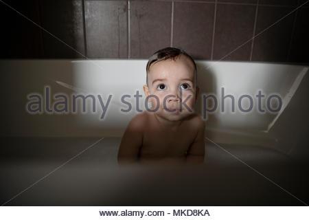 Neugierig, mit großen Augen baby boy, Bad in der Wanne - Stockfoto