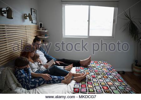 Familie lesen Bedtime Story Book auf dem Bett - Stockfoto