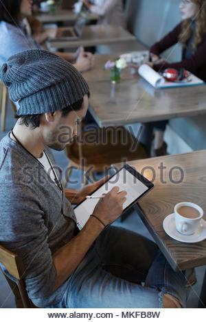 Kreative junge Menschen zeichnen, mit Stift auf digital Tablet im Cafe - Stockfoto