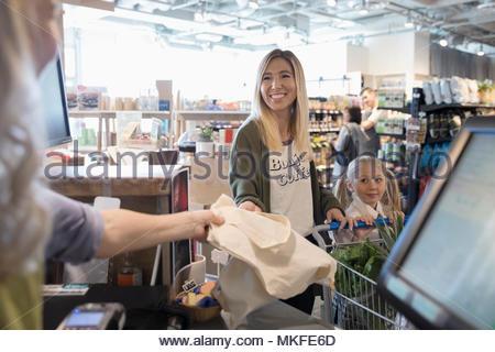 Mutter und Tochter an der Supermarkt Kasse - Stockfoto