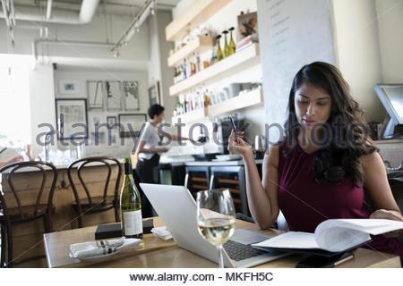 Geschäftsfrau, Wein trinken und Überprüfung von Unterlagen, am Laptop arbeiten im Cafe - Stockfoto