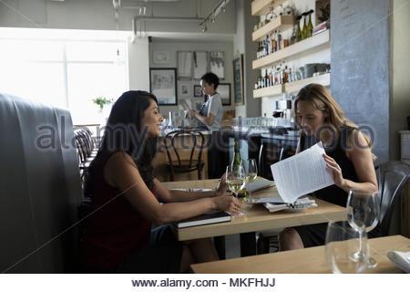 Geschäftsfrauen Schreibarbeit diskutieren, Wein geniessen bei Arbeitsessen in Cafe - Stockfoto