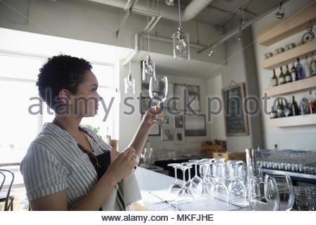 Junge Frau Kleinunternehmer trocknen Weingläser in bar - Stockfoto