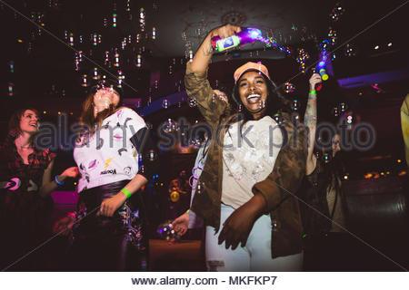 Verspielt, ausgelassenen jungen weiblichen Tausendjährigen mit Bubble Maker Tanzen im Nachtclub - Stockfoto