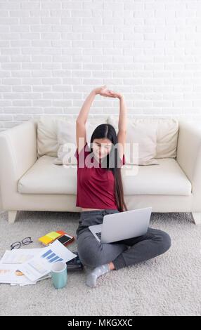 Asiatische Frau arm bis zu sich selbst Stretch nach Laptop Computer im Wohnzimmer zu Hause zu arbeiten. die Frau wieder am Sofa sitzen auf dem Teppich an der Wand arbeiten - Stockfoto