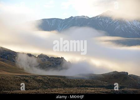 Nebel Rollen in über die Ausläufer der südlichen Alpen in Canterbury, Südinsel, Neuseeland - Stockfoto