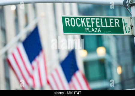 Nahaufnahme der Green street sign Darstellung ist es Rockefeller Plaza in Midtown Manhattan, New York. Verschwommen amerikanische Flaggen im Hintergrund - Stockfoto