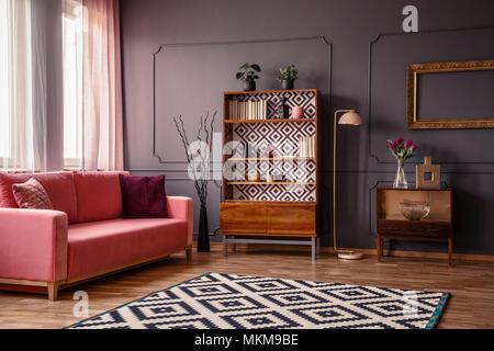 Retro Holzschrank mit Büchern und Dekorationen im dunklen Zimmer mit Rosa Sofa, Teppich und Blumen in Glasvase - Stockfoto