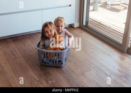 Schöne junge Kinder in einer Waschmaschine Korb, zu Hause zu sitzen. Kleines Mädchen mit Teddybär und ihr Bruder zu Hause spielt. - Stockfoto