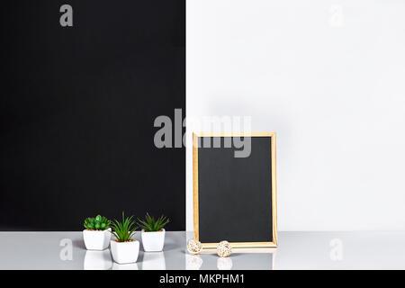 Holzrahmen mit schwarzen Platz für Text. Mock up. Stilvolle Inneneinrichtung. Grüne Pflanze in einem weißen Topf auf Schwarz-weiße Wand im Hintergrund